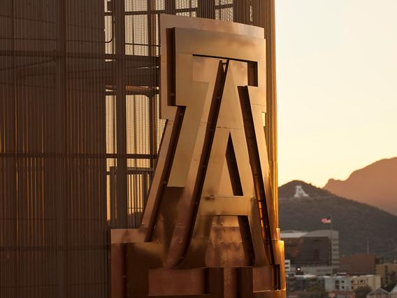 UA symbol on the side of a building with the A Mountain in the background