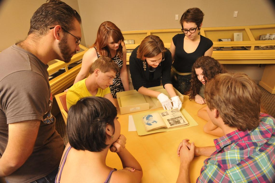A group of students and instructor examining an artifact