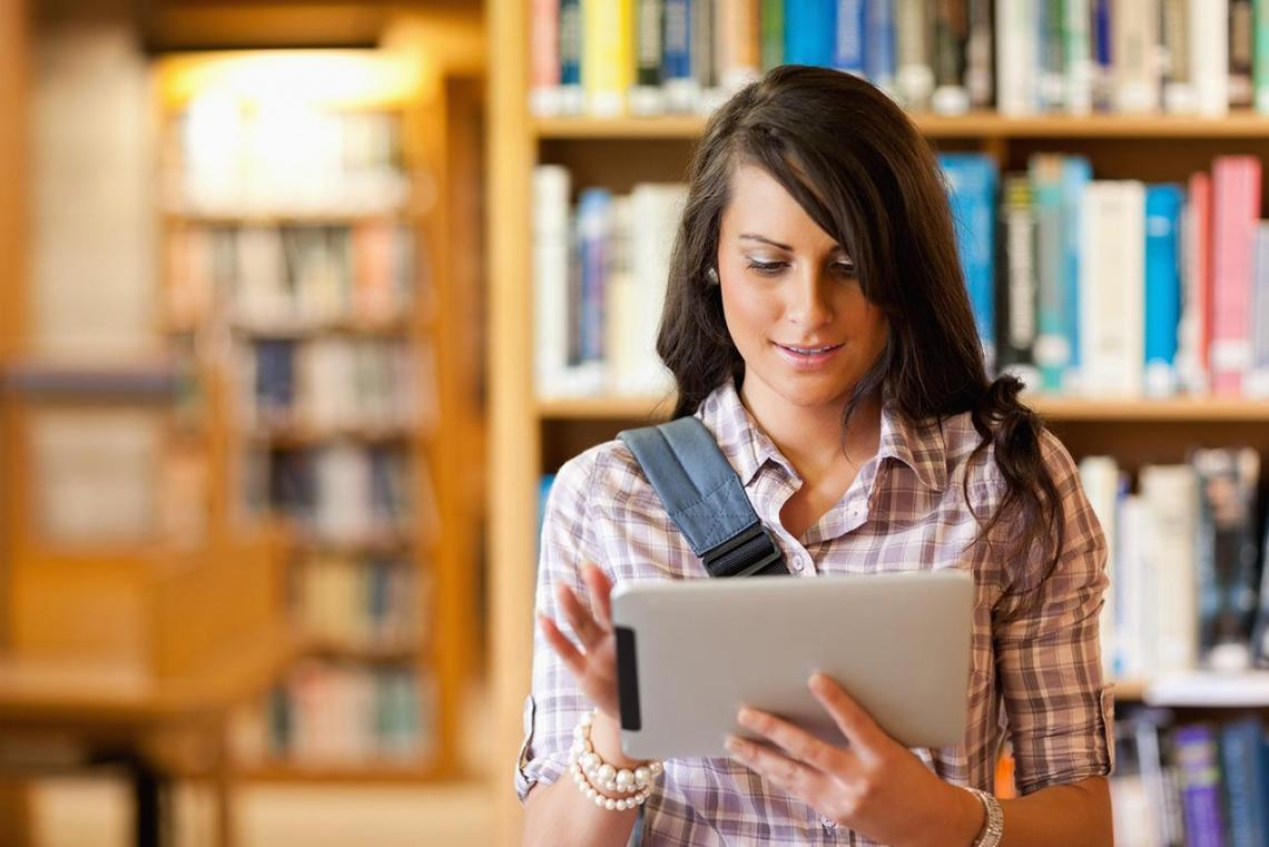 Female student in library working on tablet